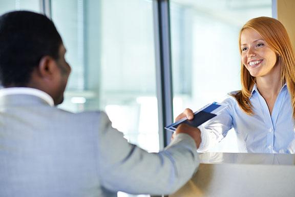 clerk handing airline tickets to businessman