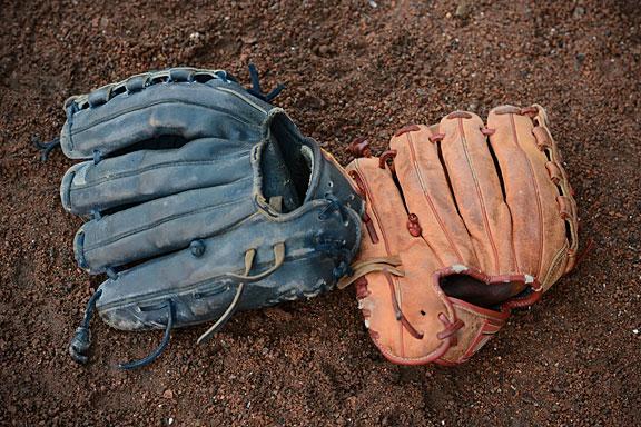 baseball gloves on brown dirt