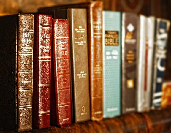 several Bible translations on a shelf