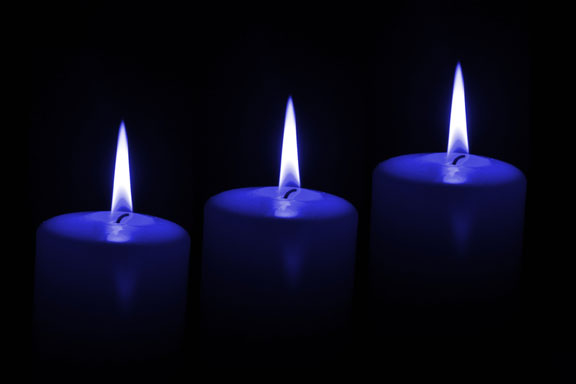 three candles on a black backgorund