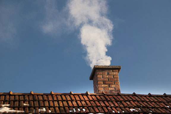 smoke pours from a chimney
