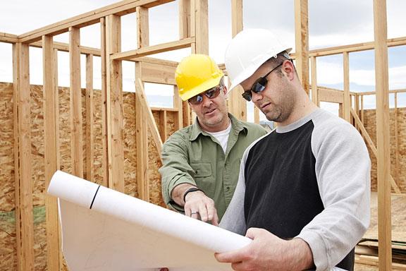 construction contractors discussing house plans