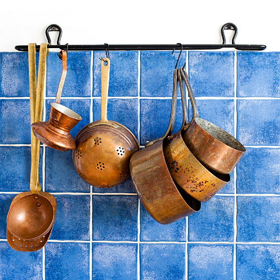 vintage copper cookware on blue tile