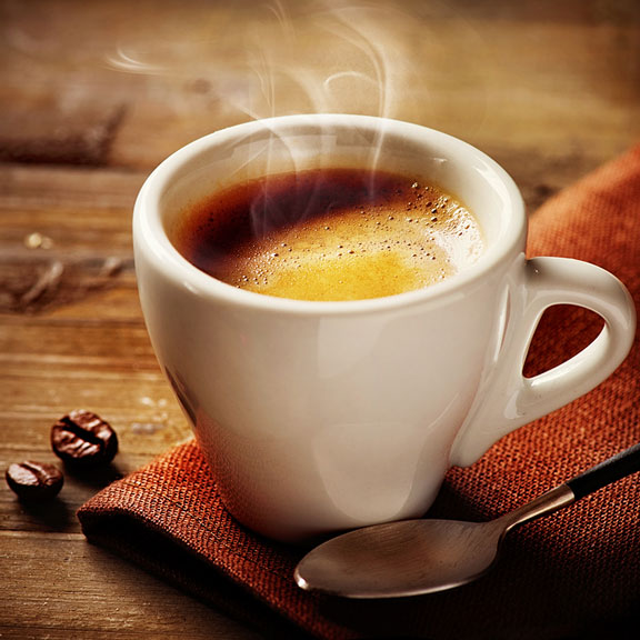 cup of espresso with two roasted coffee beans