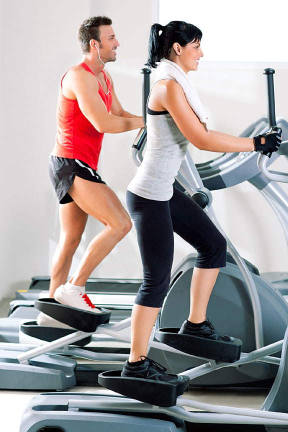 young couple working out on elliptical cross trainers