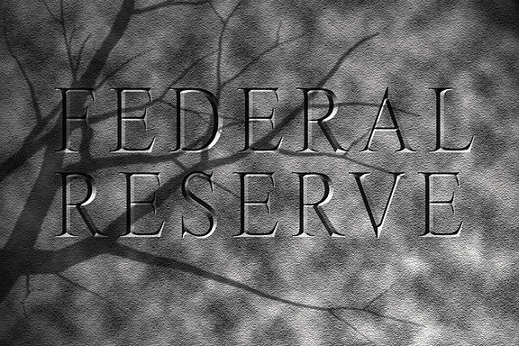 bare tree branches shadow a Federal Reserve sign