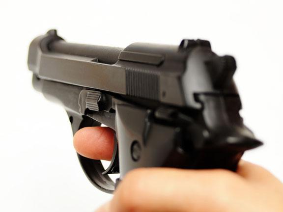 Hand Holding a Black Gun