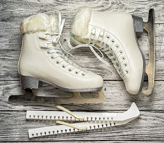white ice skates on a wooden surface