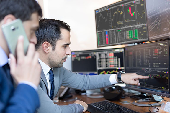 stock brokers perusing investment charts