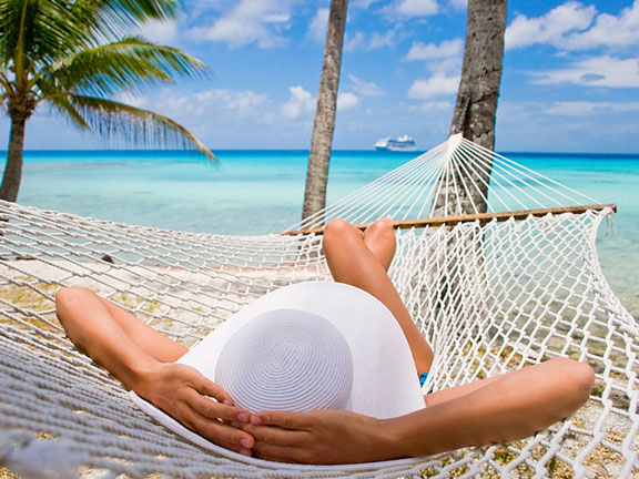 woman relaxing on a hammock under a palm tree