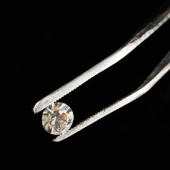 loose diamond held by tweezers