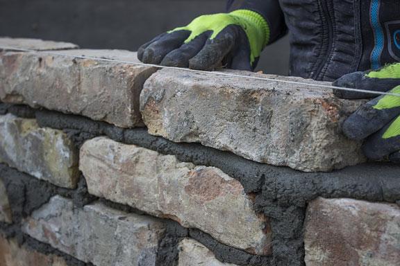 mason building a brick wall