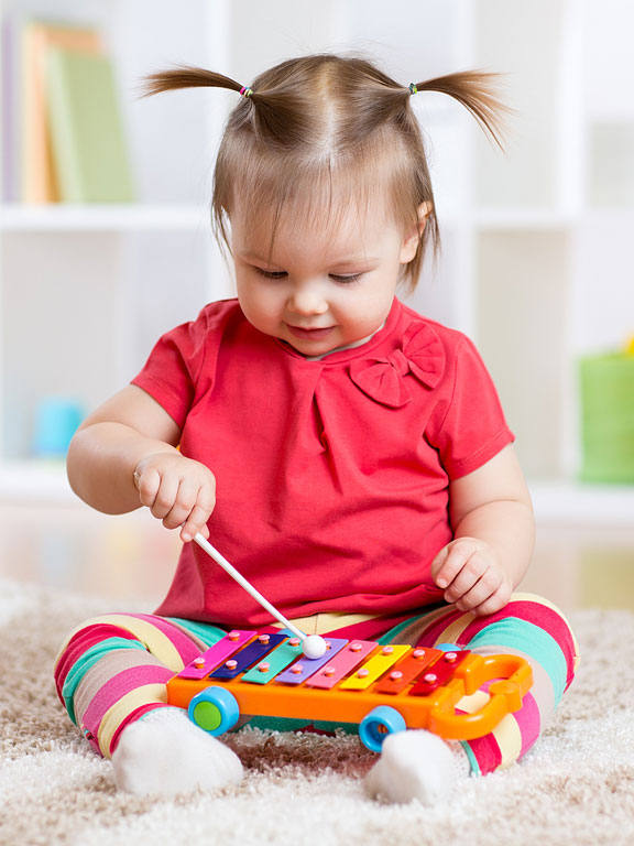 little girl playing a musical instrument