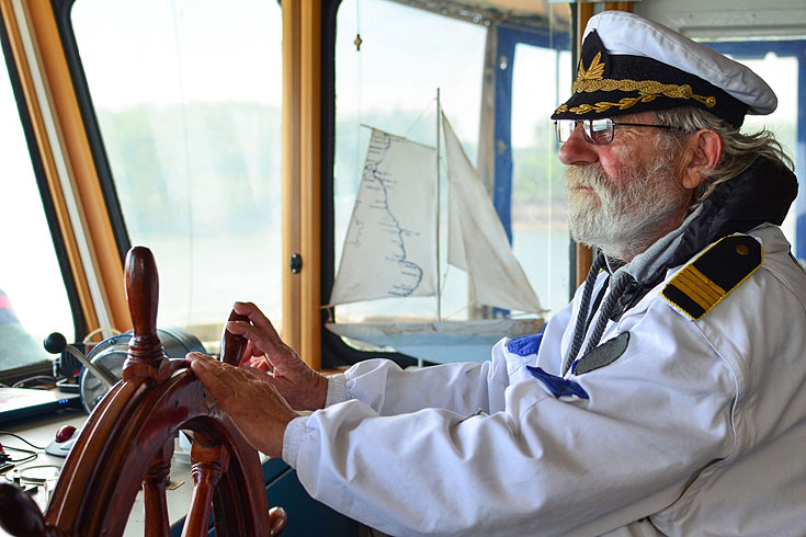 old sea captain in ship navigation cabin