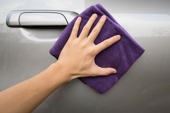 polishing a car door with a cloth