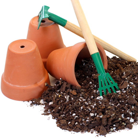 potting soil with clay pots and gardening tools