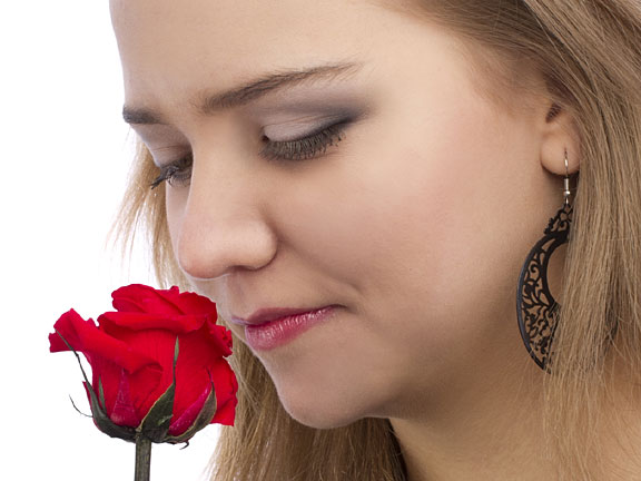 woman enjoying the scent of a rose