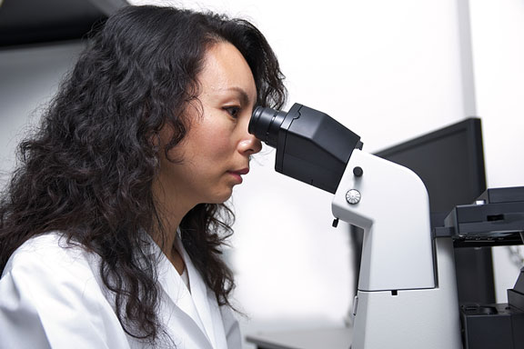 female scientist using a microscope
