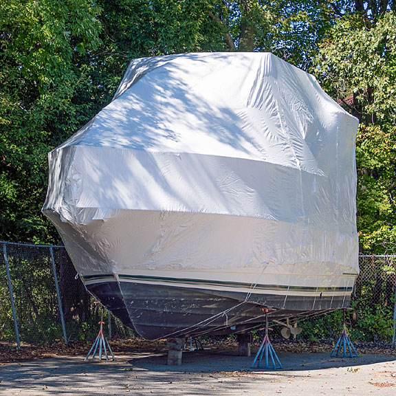 shrink-wrapped yacht on boat stands