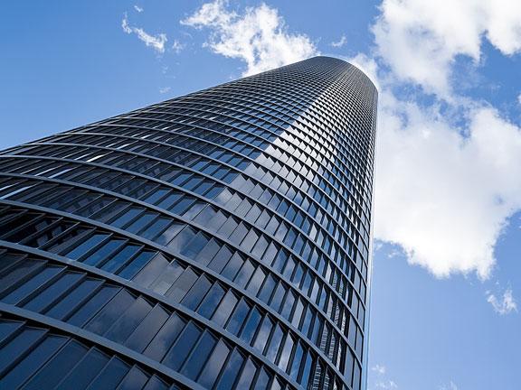 skyscraper against blue sky and white clouds