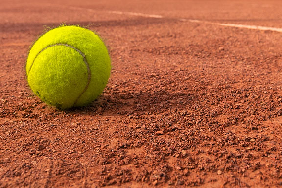 yellow tennis ball on dirt tennis court