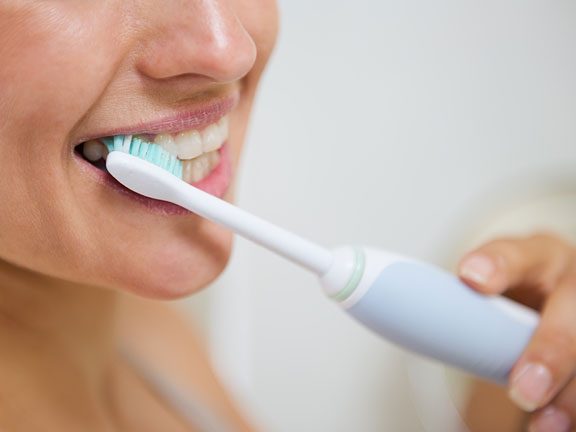 woman using an electric toothbrush