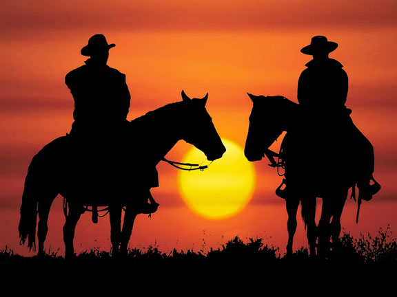 cowboy silhouettes in the sunset