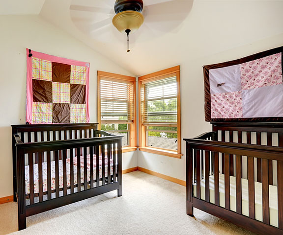 two cribs in a nursery