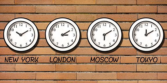 four clocks on a brick wall