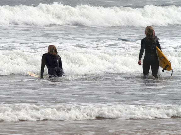 two surfers wearing wet suits